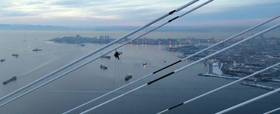 Άνδρας καθαρίζει τον πάγο από γέφυρα σε ύψος που «κόβει» την ανάσα